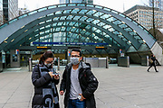 People wearing face masks standing in front of Canary Wharf underground station in London, Saturday, March 14, 2020. For most people, the new COVID-19 coronavirus causes only mild or moderate symptoms, such as fever and cough. For some, especially older adults and people with existing health problems, it can cause more severe illness, including pneumonia. (Photo/Vudi Xhymshiti)