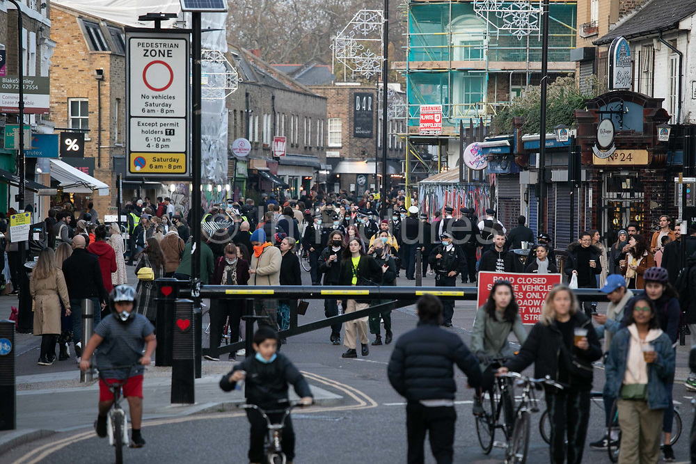 Broadway Market is teeming with people and police are asking people to move on November 7th 2020 Hackney, East London, United Kingdom. Too many people, according to social distance rules gathered in and around Broadway Market according to the lockdown restrictions of social distancing. The UK Government introduced a 4 week lockdown from November 5th - December 2nd to combat the coronavirus outbreak. It is the third day of the national lockdown and restrictions mean that people are only allowed to meet outside, in pairs and only if keeping social distance. Only if they already live together or have formed a social bubble can they interact freely.