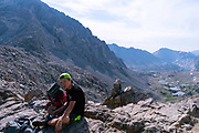 A teenage backpacker takes a break atop Pinchot Pass. John Muir Trail/Pacific Crest Trail; Sequoia Kings Canyon Wilderness; Kings Canyon National Park; Sierra Nevada Mountains, California, USA.