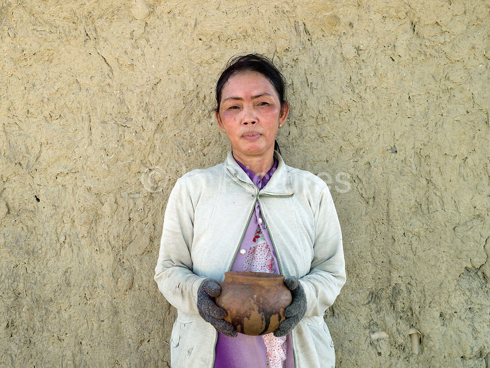 A Hindu Cham woman holds a newly-fired ceramic pot made using a traditional method outside a mud house in Duc Binh village, Binh Thuan province in Central Vietnam. Cham potters do not use a wheel to make pots, instead clay is pressed into shape using the hands. Layers of clay are added to the original piece and the potter moves around the object, pressing the clay into the desired shape. They are then put directly in the sun and completely bone dried, making them ready to be fired. Firing is done in an open pit with temperatures going up to 800 degree Celcius. The pots are arranged together and covered with layers of rice straw, which is set on fire.