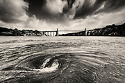 Nominated image in the 13th Black & White Spider Awards 2018<br /> <br /> Everyone who visits the area has heard about 'The Swellies' and only the experienced sailor dares take their yacht between the two famous bridges knowing full well about the infamous whirlpools that have been known to suck kayakers down into the depths before releasing them downstream! These large and very powerful whirlpools only appear at certain stages of the tide, as a massive volume of sea funnels up to the bridges. On the day we filmed this location our skipper killed the RIB engine and showed us just how quickly we could be spun around and pulled towards the vortex. It was both awe inspiring and eerie and a spectacle to remember. <br /> <br /> In the background stands the Telford Suspension Bridge, completed in 1826, the first of the two marvels of industrial engineering that finally allowed people and traffic to cross from mainland Wales to Anglesey without the need for ferries. Many people lost their lives crossing the treacherous Menai Strait on small boats and ferries before the bridges were built.