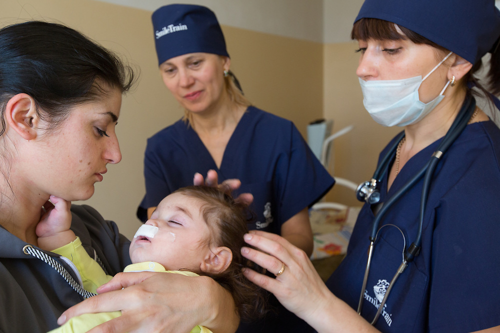 CAPTION: As Armena gazes at her sleeping daughter, Dr Fomenko and anaesthetist Lubov Kalganova talk her through some of things she'll need to do to care for her over the coming days and weeks. LOCATION: Volgograd City Hospital #1, Volgograd, Russia. INDIVIDUAL(S) PHOTOGRAPHED: Armena Vardanan (left), Dr Irena Fomenko (centre, above), Stella Aharonyan (centre, below) and Lubov Kalganova (right).