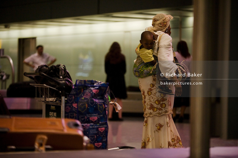 Young child on mother's back await baggage from African flight at Heathrow Airport's Terminal 5.