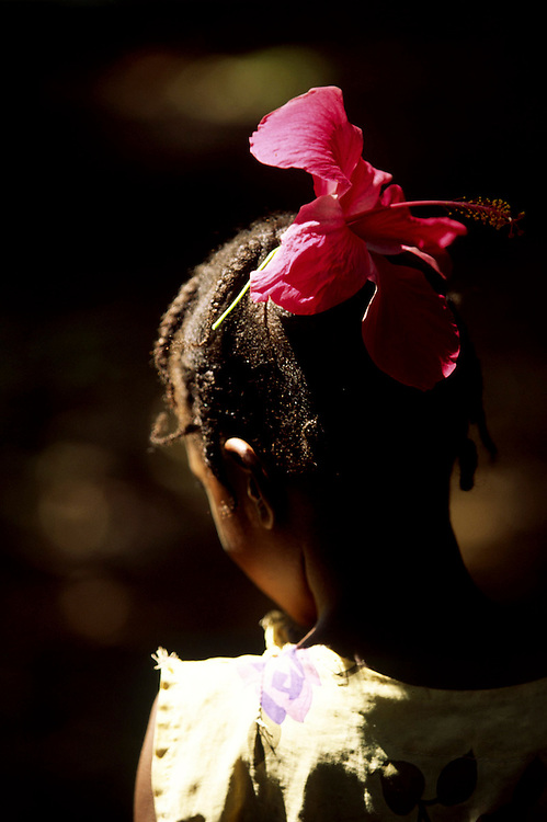 Little girl wearing a flower in her hair. The tiny Ilheu das Rolas (Pidgeon Island) is on the southern tip of Sao Tome island and it has a Resort and a fisherman village.