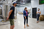 "22 JULY 2020 - AMES, IOWA: ELLIOT THOMPSON, owner of Alluvial Brewing, left, talks to THERESA GREENFIELD, center, about the needs of small businesses during a visit by Greenfield to Alluvial Brewing in Ames, IA. Greenfield, a Democrat, is running for the US Senate against incumbent Republican Senator Joni Ernst. Recent polls have Greenfield slightly ahead of or statistically tied with Ernst, who is closely allied with President Donald Trump. Although Greenfield is not doing much in person campaigning with big events, she is meeting with business people across the state of Iowa to promote her ""Small Towns, Bigger Paychecks"" economic program.       PHOTO BY JACK KURTZ"