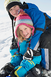 Portrait of brother and sister sledging, smiling, Bavaria, Germany