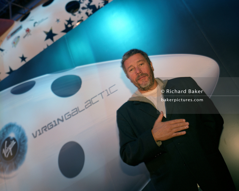 Designer Phillippe Starck standing at the nose of Virgin Galactic's SpaceShipTwo during its unveiling at the New York Wired NextFest at the Jacob K. Javits Convention Center. Starck is design consultant for Virgin's space company and for SpacePort America, New Mexico, USA.  Aboard the re-usable space vehicle will be 6 passengers, each of whom will have paid $200,000 for the 40 minute flight to 360,000 feet (109.73km, or 68.18 miles) and to experience just 6 minutes of weighlessness.  Flights start around 2009/10 from a Mojave desert test facility but therafter, at the new Starck-designed SpacePort America, New Mexico, USA. a 27 square mile, $225 million headquarters and mission control facility near Las Cruces.  .