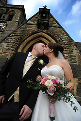 A couple kiss outside the church, just married.MODEL RELEASED