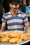 A man with a tray of fresh jalebi at the Old and Famous Jalebi Wala (at the corner of Dariba Kalan and Chandni Chowk). Delhi, India