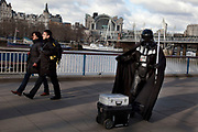 A walk along the River Thames on the Southbank in London. A street entertainer arrives, dressed as Darth Vader from the movie Star Wars. This area is very popular especially on the weekends for Londoners to walk and see different arts, culture and entertainment.