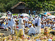 20 JULY 2016 - KUSAMBA, BALI, INDONESIA:   Hindu priests lead a service on Kusamba beach. Several hundred Balinese Hindus gathered on the beach in Kusamba, Bali, for a ceremony to honor the full moon. They prayed for more than hour and then community leaders threw an offering into the ocean.      PHOTO BY JACK KURTZ