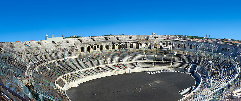 Interior of the Arena of Nemes, a Roman Ampitheatre built around 70 AD during the reign of Emperor Augustus, Nimes, France . The Arena of Nîmes is a Roman amphitheatre, situated in the French city of Nîmes. Built around 70 CE, shortly after the Coliseum of Rome, it is one of the best-preserved Roman amphitheatres in the world.  The Arena of Nîmes is 133 meters long (145 yards) and 101 meters wide (110 yards), with an arena measuring 68 meters (74 yards) by 38 meters (32 yards). The outer facade of the Arena of Nîmes is 21 meters high (69 feet) with two stories of 60 arcades. .<br /> <br /> Visit our ROMAN ART & HISTORIC SITES PHOTO COLLECTIONS for more photos to download or buy as wall art prints https://funkystock.photoshelter.com/gallery-collection/The-Romans-Art-Artefacts-Antiquities-Historic-Sites-Pictures-Images/C0000r2uLJJo9_s0