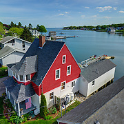 Take from around 40 feet up, this single real estate marketing image captures the home's street setting, complex shape, dock, and direct proximity to the cove with views out to the sea.