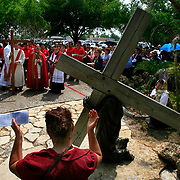 Maria Servin, lower left, prays with alongside a statue depicting the first time Jesus fell while carrying the cross during the Stations of the Cross at the Basilica of Our Lady of San Juan Del Valle. Hundreds of people participated in the procession that tells the story of Jesus' crucifixion in 14 stations across the basilica grounds. <br /> Nathan Lambrecht/The Monitor