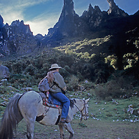 A member of a  National Geographic archaeology expedition rides his horse below the Pumasilla (Puma's Claws) peaks above Quebrada Moyoc, a deep valley in  Peru's Cordillera Vilcabamba mountains.
