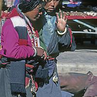 CHINA, TIBET. Village girls circle Jokhang Temple through Lhasa's Barkhor Bazaar.