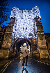 December 20, 2017 - York, West Yorkshire, UK - A Young Lady takes a selfie as she stands infront of one of the Illuminated Historic Gates at the City of York, Yorkshire United Kingdom  (Credit Image: © Charlotte Graham via ZUMA Wire)