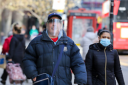 © Licensed to London News Pictures. 23/03/2021. London, UK. A man wearing a visor in Wood Green, north London on the anniversary of the first Covid-19 lockdown in the UK. The next key date for restrictions easing is Monday 29 March 2021, when the 'Stay at Home' guidance will be dropped. Photo credit: Dinendra Haria/LNP