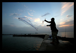 29 August 2006 - New Orleans - Louisiana. Lakeview. Lake Pontchartrain. Local fishermen cast their nets and land catfish from the still waters that just 12 months ago devastated the area as they filled back into the city, rupturing the nearby 17th street canal. The connection New Orleans and south Louisiana has with the water is inextricable. The two are forever linked together and until the Army Corps of Engineers is able to build sufficient flood protection, and the greater world is able to control global warming and rising seas, the city and the region will continue to be at increased risk for even greater devastation in the years ahead.