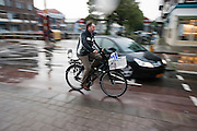 Een man rijdt in de regen op de fiets en moet uitkijken voor een auto die de weg op komt rijden.<br /> <br /> A man is riding in the rain on his bike.