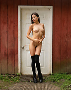 Nude woman wearing black stockings standing outside in front of a white barn door.