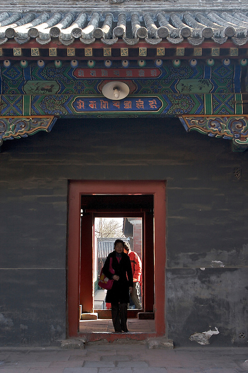 A side doorway in Yonghegong. This Tibetan Temple is known to tourists as Lama Temple and it's located in Dongcheng District Beijing, China. This is the largest Temple of its kind outside of Tibet.  In 1723 the structure was turned into a Temple after the resident became the third Qing Emperor.