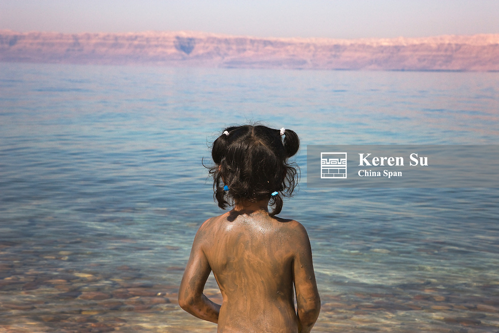 Girl covered with mud by Dead Sea, Jordan