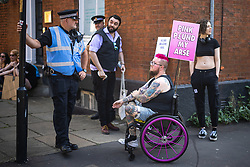 """© Licensed to London News Pictures . 28/08/2021. Manchester, UK. A protester with a placard reading """" Pink pound my arse """" talks with a police officer at the demonstration . People take part in a Reclaim Pride march through Manchester City Centre , in opposition to the management of the city's """"official"""" Manchester Pride charity festival . The Manchester Pride charity parade was cancelled in 2020 due to Coronavirus . An """"equality march"""" organised by Manchester Pride charity was due to take place on Deansgate as the protest passed through the Gay Village . Protesters object to Manchester Pride charity's withdrawal of funding for the LGBT Foundation's condom distribution scheme and HIV charity George House Trust as well as increasing commercialisation of the annual event . Photo credit: Joel Goodman/LNP"""
