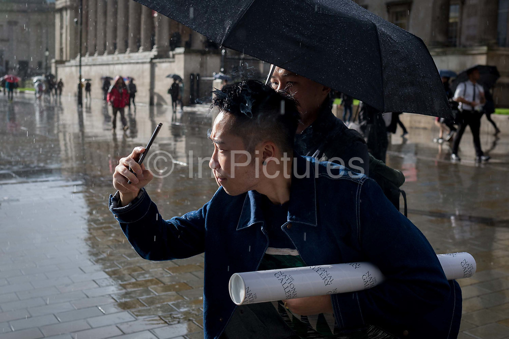Helped by a friend with an umbrella, a visitor to the nearby National Gallery concentrates hard on taking a photo of Trafalgar Square after an autumnal downpour in central London, on 1st October 2019, in London, England.