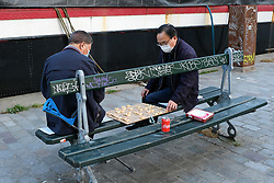 Men playing a game on a bench are seen in Paris during COVID-19 as a strict lockdown is effective to stop the spread of the Coronavirus disease. Shot in Paris, France on April 27, 2020. Photo by Aurore Marechal/ABACAPRESS.COM