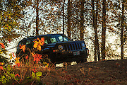 USA, Oregon, Scio, Jeep Patriot on rural road in OR at sunset.