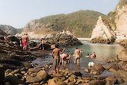 Tourists frolick in a swimming hole set against dramatic cliffs along the rocky coastline near Maruata Bay, Michoacan State, Mexico.
