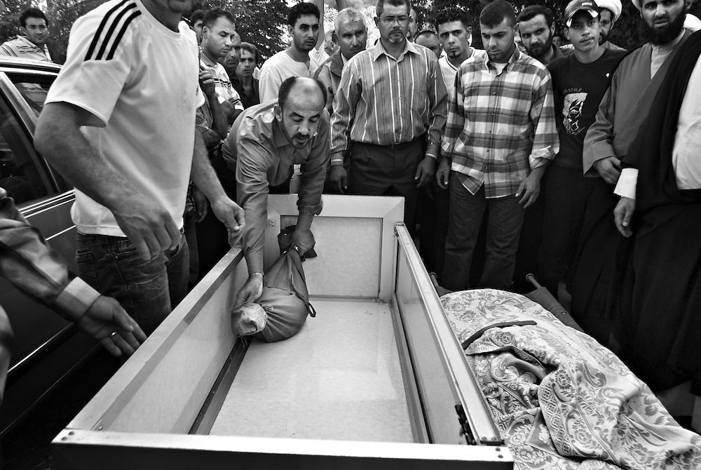 Friends and relatives gather to bury the body of one of Sayeed Adel Akkash's ten children in the village of Dweir near Nabatiyeh, southern Lebanon, July 13, 2006. Israeli forces targeted Sayeed Akkash's house in the middle of the night, killing the Sayeed, his wife and their ten children. Israeli forces intensified their attacks in Lebanon, with airstrikes that blasted the country's only international airport and the Hezbollah TV station in what was Israel 's heaviest air campaign against Lebanon for 24 years.
