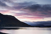 Clouds tinged with the pink of sunset over Ballachulish Bridge at the mouth of Loch Leven, with the Ardgour mountain range shrouded by the clouds beyond.