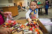 Girl Scout Riley Lancaster, 4, packages candy for the U.S. Military during the Girl Scout USA of Northern California Operation Holiday Cards packing event at Mount Olive Ministries in Milpitas, California, on November 18, 2015. (Stan Olszewski/SOSKIphoto)