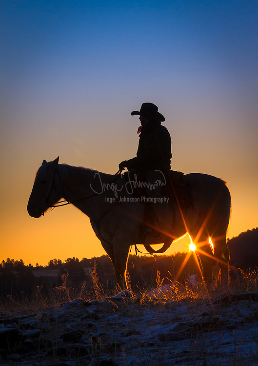 Cowboy on horse silhouetted against the rising sun and morning sky in eastern Wyoming