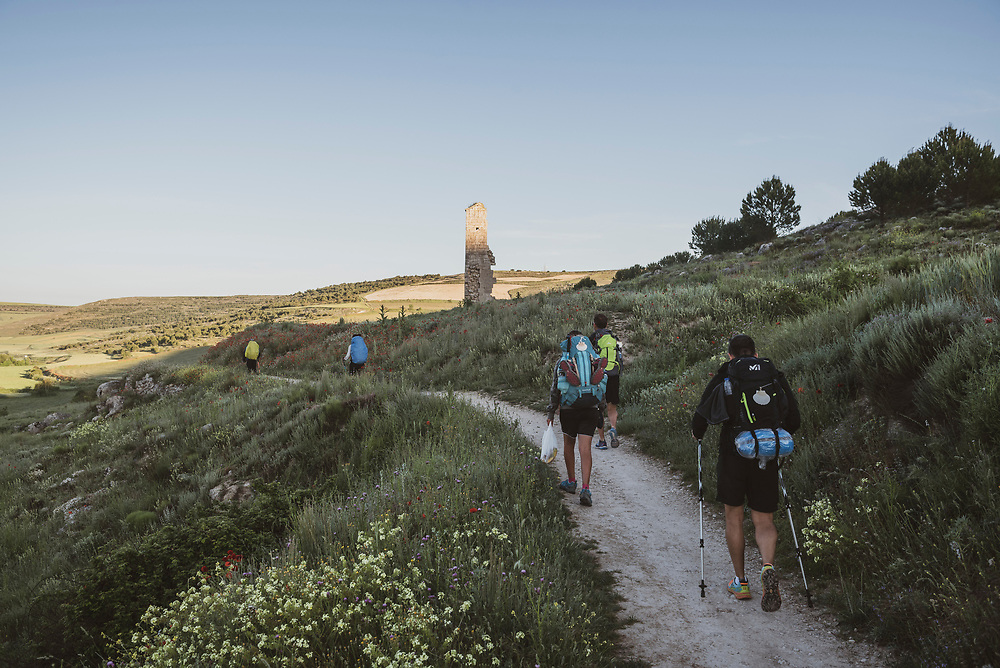 Pilgrims on the Camino de Santiago hiking out of the small town of Hontanas at sunrise. (June 16, 2018)