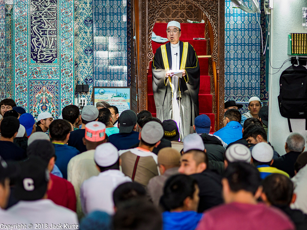 """15 JUNE 2018 - SEOUL, SOUTH KOREA: The Imam delivers the """"Khutbah,"""" or sermon, at Seoul Central Mosque on Eid al Fitr, the Muslim Holy Day that marks the end of the Holy Month of Ramadan. There are fewer than 100,000 Korean Muslims, but there is a large community of Muslim immigrants in South Korea, most in Seoul. Thousands of people attend Eid services at Seoul Central Mosque, the largest mosque in South Korea.   PHOTO BY JACK KURTZ"""