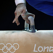 A gymnast performs on the Pommel Horse showingLondon Olympic sugnage during the Men's Artistic Gymnastics podium training at North Greenwich Arena during the London 2012 Olympic games preparation at the London Olympics. London, UK. 25th July 2012. Photo Tim Clayton