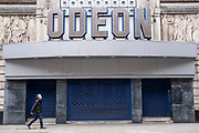 Closed with shutters down, the Odeon cinema on Shaftesbury Avenue as the national coronavirus lockdown three continues on 5th March 2021 in London, United Kingdom. With the roadmap for coming out of the lockdown has been laid out, this nationwide lockdown continues to advise all citizens to follow the message to stay at home, protect the NHS and save lives, and the streets of the capital are quiet and empty of normal numbers of people.