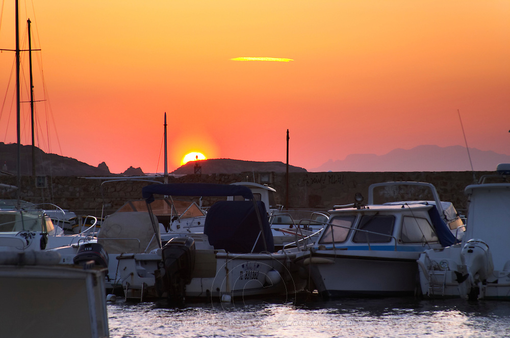 The harbour at sunset, boats moored at the key side, sun setting behind the mountains Le Brusc Six Fours Var Cote d'Azur France