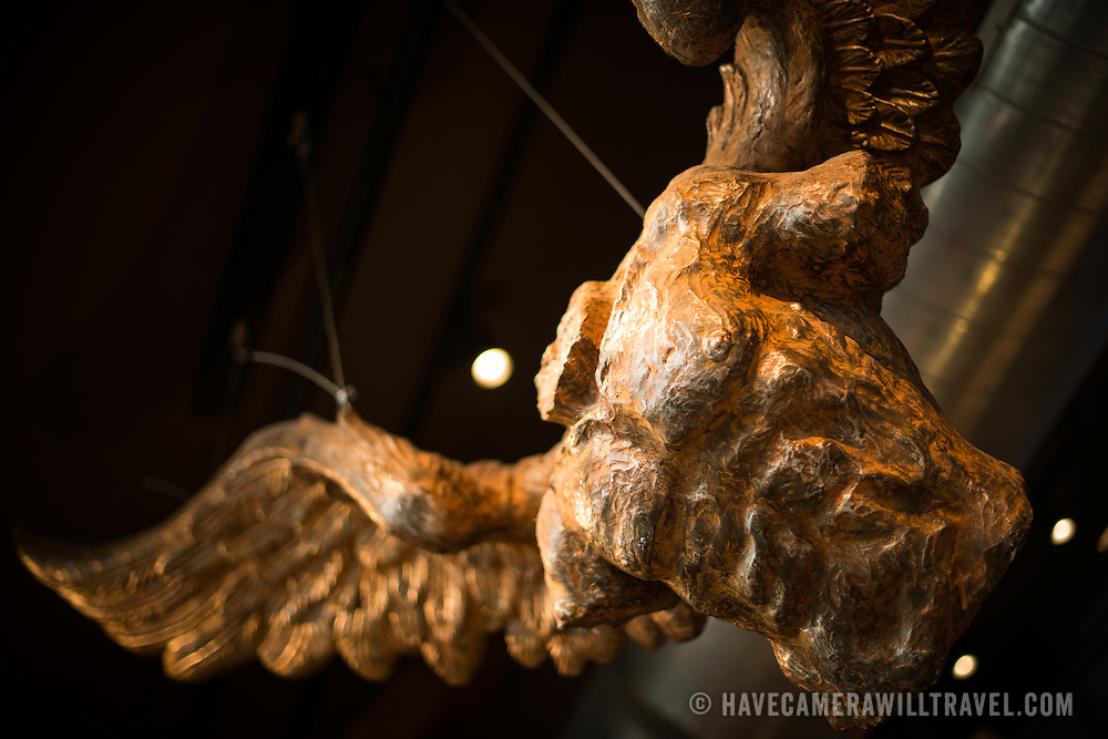 A stylized statue of a headless angel hanging from a ceiling in a restaurant.