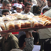 A bread vendor carts his wares over the heads of thoudsands of demonstrators in Cairo's Tahrir Square.