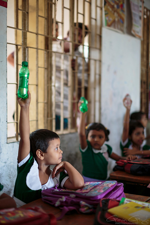 A schoolgirl holding a bottle containing clean water raises her hand during a class
