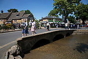 Bourton on the Water in The Cotswolds, United Kingdom. Bourton-on-the-Water is known for its picturesque High Street, flanked by long wide greens and the River Windrush that runs through them. The river is crossed by several low, arched stone bridges. These arched bridges have led to Bourton-on-the-Water being called the 'Venice of the Cotswolds'. Bourton-on-the-Water often has more visitors than residents during peak times of the tourist season. The Cotswolds is an area in south central England. The area is defined by the bedrock of limestone that is quarried for the golden coloured Cotswold stone. It contains unique features derived from the use of this mineral; the predominantly rural landscape contains stone-built villages and historical towns.