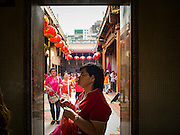 "08 FEBRUARY 2016 - BANGKOK, THAILAND:  People pray in a doorway on Chinese New Year at Wat Mangon Kamlawat, the largest Mahayana (Chinese) Buddhist temple in Bangkok during the celebration of the Lunar New Year. Chinese New Year is also called Lunar New Year or Tet (in Vietnamese communities). This year is the ""Year of the Monkey."" Thailand has the largest overseas Chinese population in the world; about 14 percent of Thais are of Chinese ancestry and some Chinese holidays, especially Chinese New Year, are widely celebrated in Thailand.      PHOTO BY JACK KURTZ"