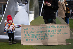 """© Licensed to London News Pictures. 06/12/2020. Manchester, UK. A child stands next to a cardboard placard reading """" Wake up sheep new normal = new world order Bill Gates' vaccine mark of the beast No to UN Agenda 21 , genocide and a cashless society. No to taking the knee , save our children """" . An anti lockdown protest against measures imposed by the British government , designed to limit the spread of Coronavirus , takes place in Piccadilly Gardens in Manchester City Centre . Photo credit: Joel Goodman/LNP"""