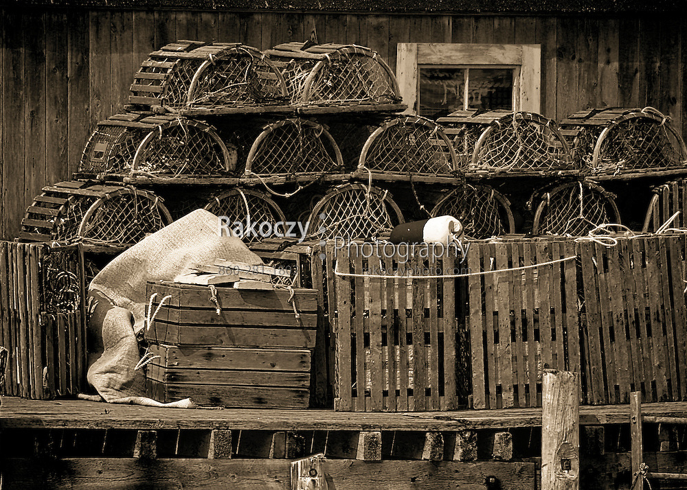Old wooden lobster pots are stacked against the weathered side of a shack in the fishing village of Peggy's Cove in Nova Scotia, Canada.