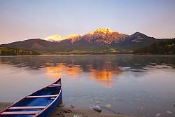 Canoe at Pyramid Lake as the alpenglow of an autumn dawn kisses Pyramid Peak in Jasper  National Park