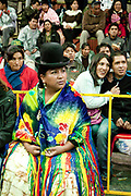 Female wrestler in crowd with travellers in background. Lucha Libre wrestling origniated in Mexico, but is popular in other latin Amercian countries, including in La Paz / El Alto, Bolivia. Male and female fighters participate in the theatrical staged fights to an adoring crowd of locals and foreigners alike.